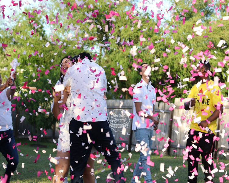 Couple hugging joyfully as they are showered with pink gender reveal confetti cannons