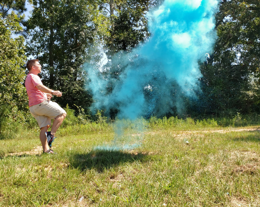 Individual kicking blue powder filled soccer ball outside.