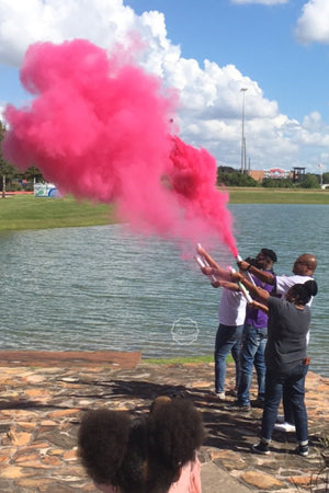 Family  and Friends gather around the lake to announce it's a girl with our pink gender reveal powder cannon