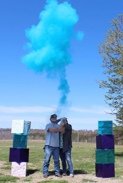 Couple posing under a cloud of blue powder.