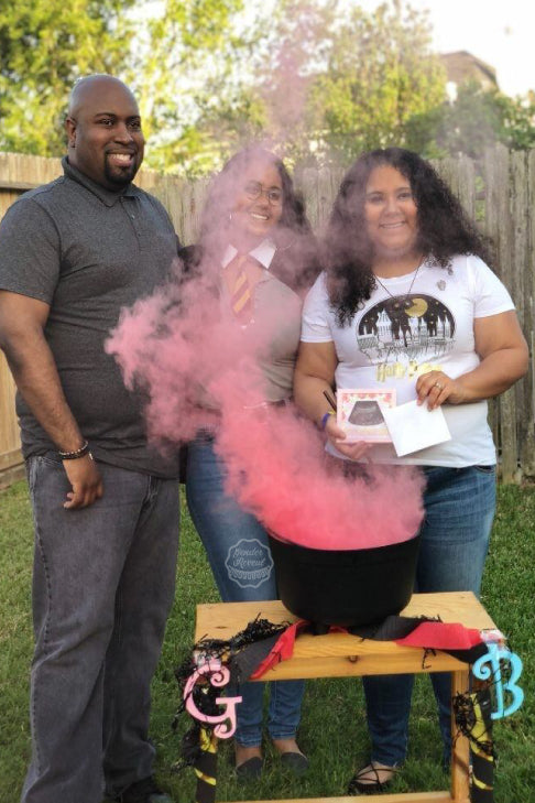 This family poses for a delightful picture they will cherish forever as they reveal the baby to be is a girl by using our pink gender reveal smoke bomb
