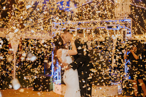 Couple posing at a wedding while gold confetti falls all around them.