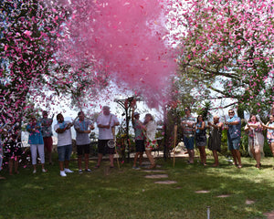 These friends and family added pink gender reveal powder and confetti cannons to their Hawaiian themed gender reveal
