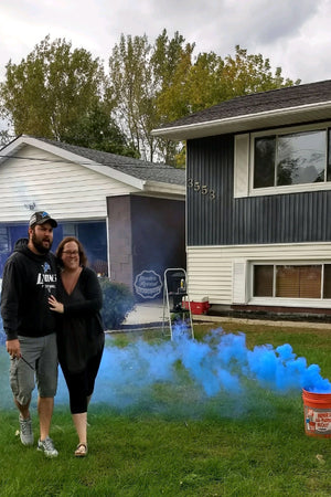 These soon to be parents are captivated by the cloud of smoke that comes from our blue gender reveal smoke bombs revealing they are having a boy