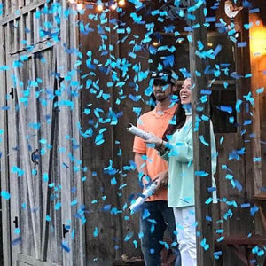 Couple is showered with blue confetti cannons at their gender reveal
