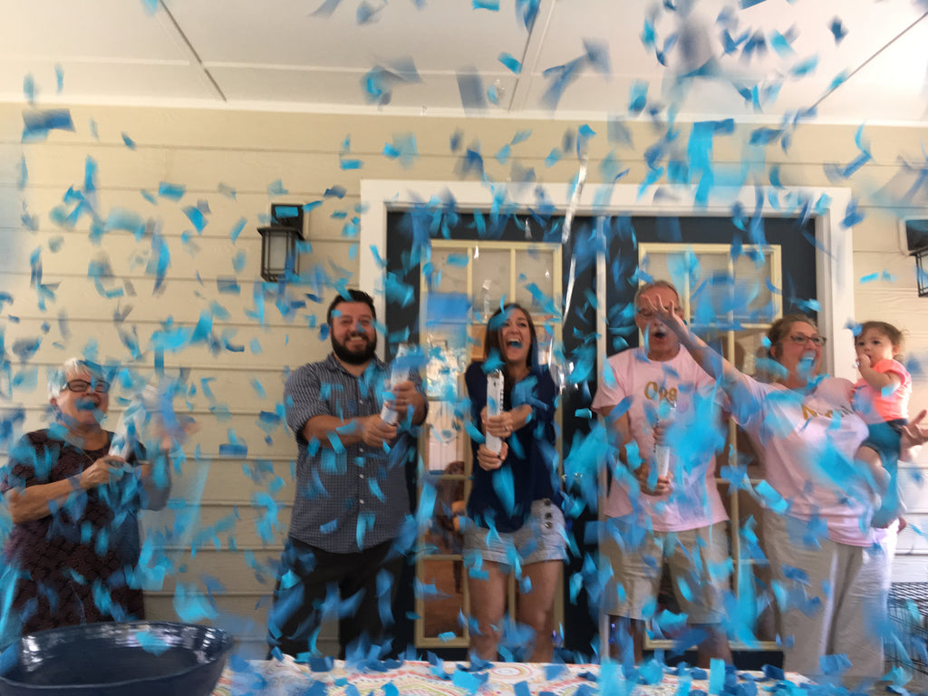 Couple posing with family while shooting blue confetti everywhere.