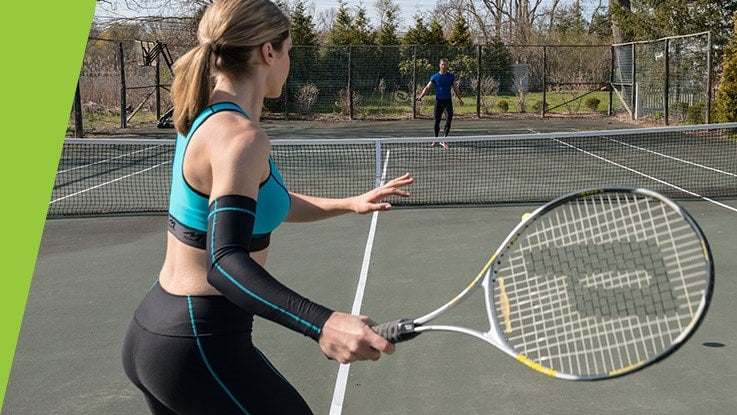 A man and woman playing tennis in their Marena Sport compression activewear