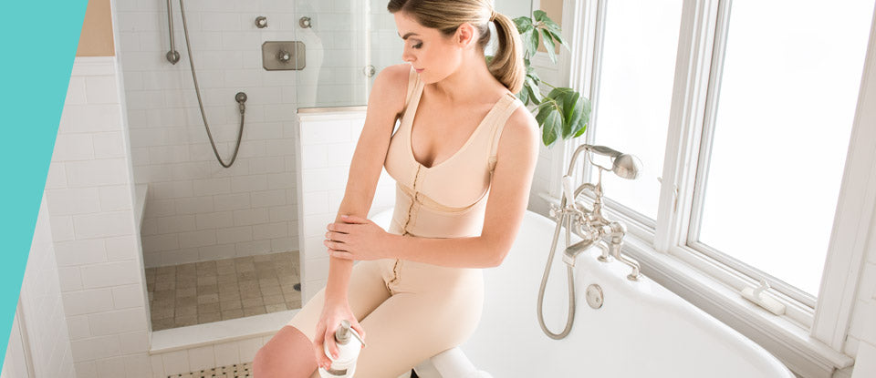 A woman sits by the bathtub in her compression bodysuit from Marena Recovery