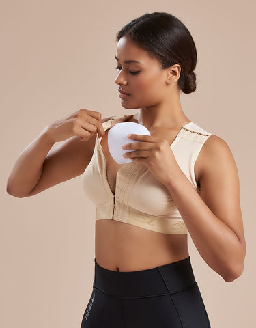 Marena Recovery B16P pocket bra showing a model inserting a prosthesis into the pocket.