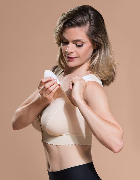 Marena Recovery BR bra side view in beige showing model closing adjustable velcro shoulder straps.