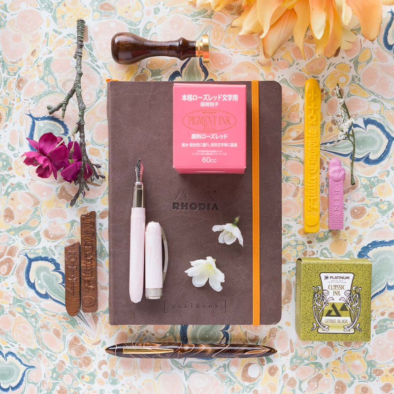 A product layout inspired by Alphonse Mucha, featuring a Visconti Rembrandt Fountain Pen in Pink
