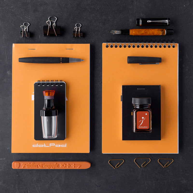 A product layout inspired by Ancient Greek pottery, featuring a Rhodia No. 16 Top Wirebound Notebook in Orange