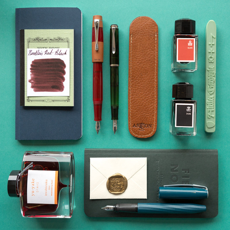 An Edward Hopper themed product layout featuring the Aston Leather Single Slip Pen Pouch in Tan