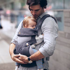 A man carries a sleeping baby on his front in a carbon grey ergo 360 performance carrier.
