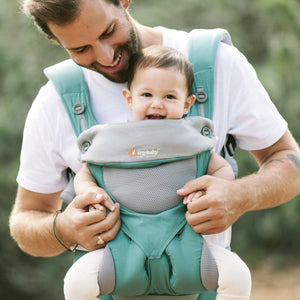 A man looks down at a baby in an ergo 360 performance carrier who is facing out at the world with legs in an ergonomic M position