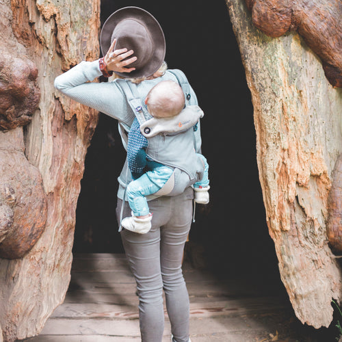 A woman carries an older baby on her back in an ergonomic Ergo 360 baby carrier.