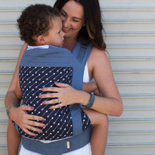Woman carries a toddler facing in wards on her front in a Beco Toddler carrier in Arrow design