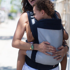 Woman carries a toddler facing inwards on her front in a Beco Toddler carrier in Cool breeze mesh