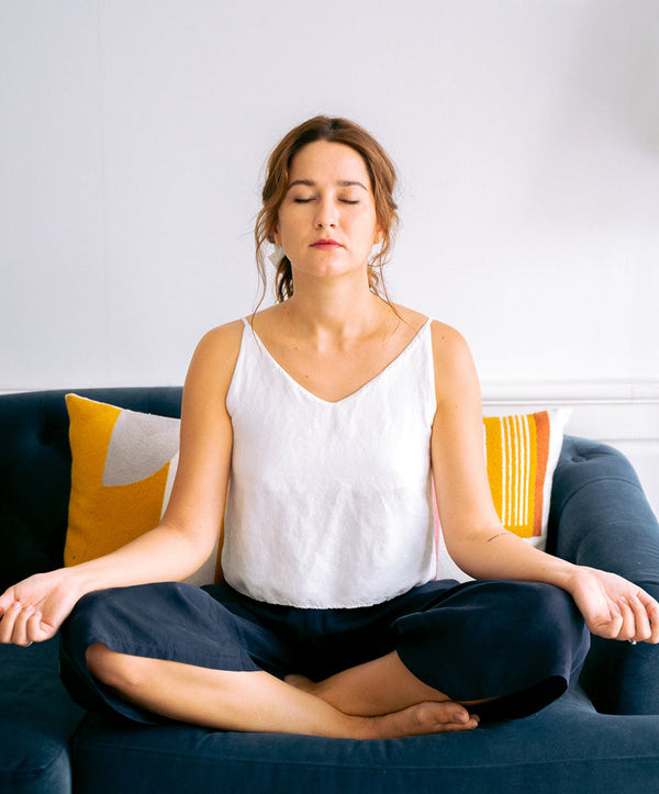 Woman meditating on a sofa