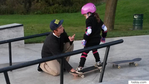 Dad teaching skating to kids using Skateboards