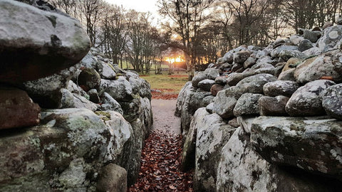 Sun aligning with clava cairns ancient pagan celtic stones at the winter solstice