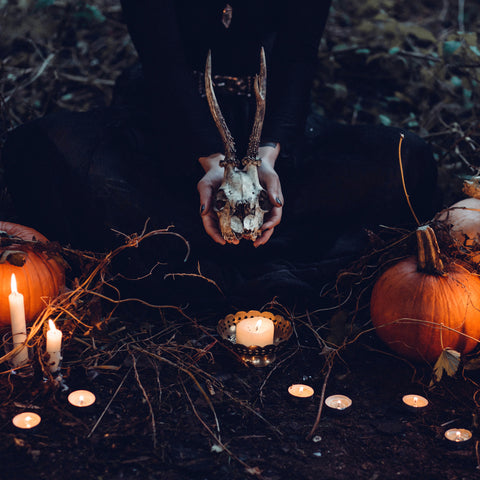pagan spell ritual, witch kneeling on the ground holding animal skull and surrounded by a circle of candles