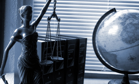 Lady justice holding a scale with legal books and globe in the background