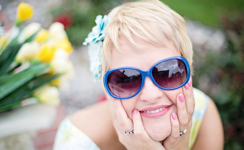 a happy young woman in blue sunglasses with tulips in the background