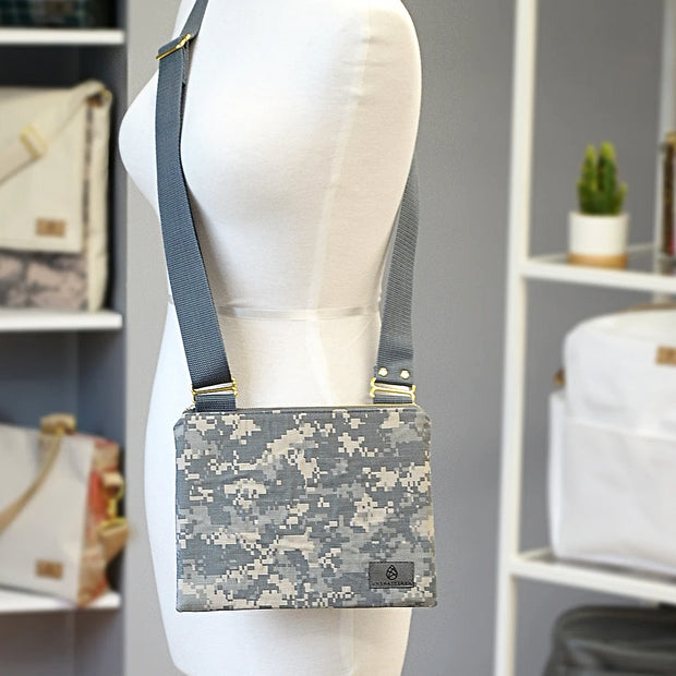 A U.S. army zippered crossbody bag hanging on a mannequin in front of a shelf of other bags.