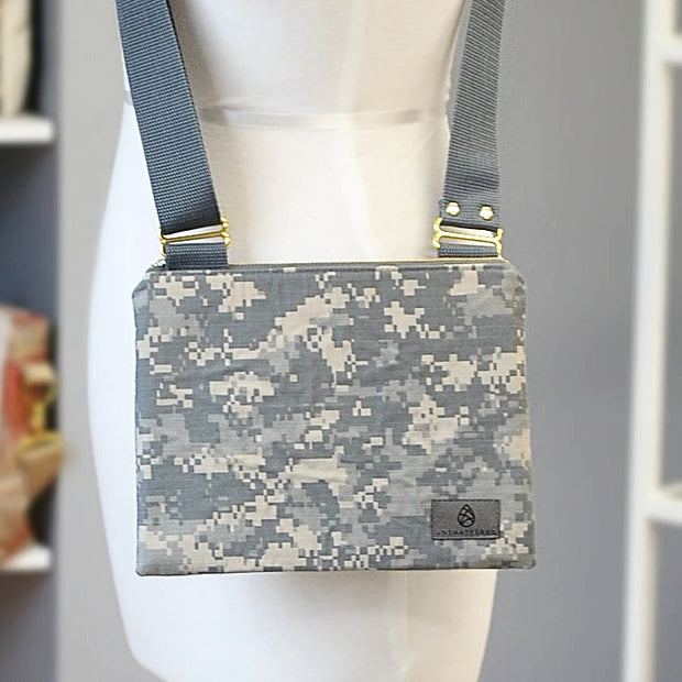 A U.S. army zippered crossbody bag with gray straps in front of a gray background.