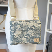A U.S. Army zippered crossbody bag with tan straps in front of a gray wall.