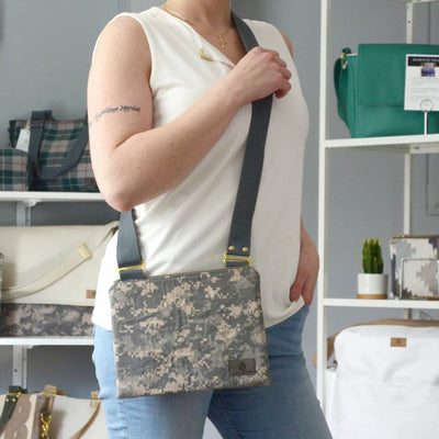 A U.S. Army zippered crossbody bag being worn by a woman wearing a white tank top inside a boutique.