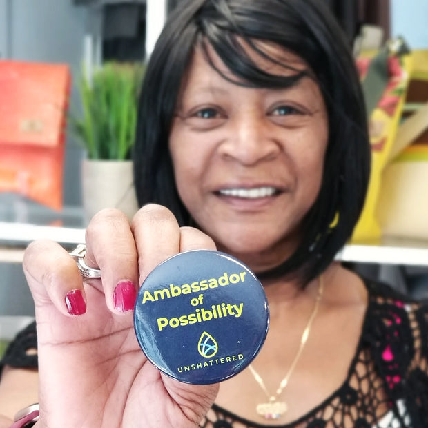 One Ambassador of Possibility button held by a woman.