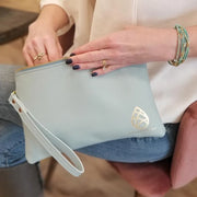 Kelly Lyndgaard holding a limited edition leather zip wristlet as she sits on a chair.