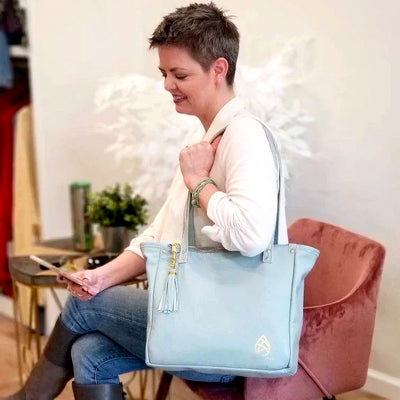 Kelly Lyndgaard sits on a chair with one founders edition leather tote over one shoulder.