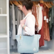 Kelly Lyndgaard holding one founders edition leather tote in front of a rack of clothing.