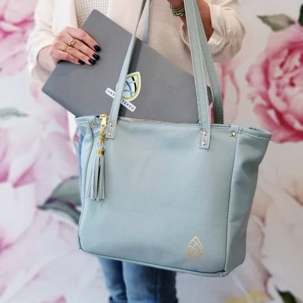 Kelly Lyndgaard puts one laptop inside of one founders edition leather tote in front of a floral background.