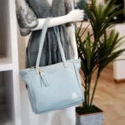 One founders edition leather tote over the arm of a mannequin next to a potted plant.