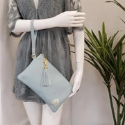 One founders edition leather wristlet hanging  on a mannequin's arm next to a plant.