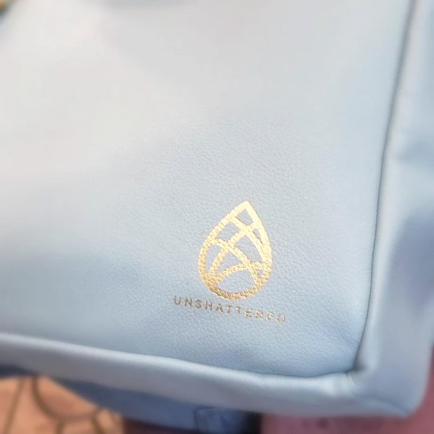 Gold-tone embossed Unshattered logo on one founders edition leather tote.