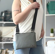 One gray, vinyl, zippered crossbody bag held by a woman in a white shirt in a boutique.