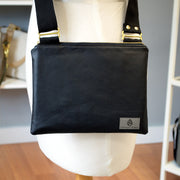 One black vinyl zippered crossbody bag hanging on a mannequin in front of a gray wall.