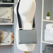 One gray vinyl zippered crossbody with a black strap hanging on a mannequin in front of shelves of other bags.