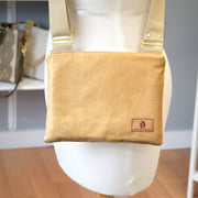 One tan vinyl zippered crossbody with a tan strap hanging on a mannequin in front of a gray wall.