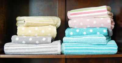 spotted and striped towels neatly folded on a bathroom shelf