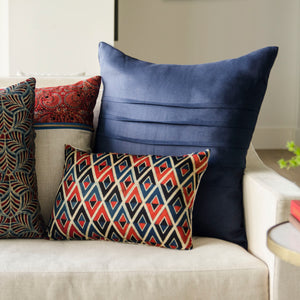 red and blue decorative throw lumbar pillow. Handmade and block printed on a silk cotton fabric by artisans in India. Designed for the well travelled, modern consumer.