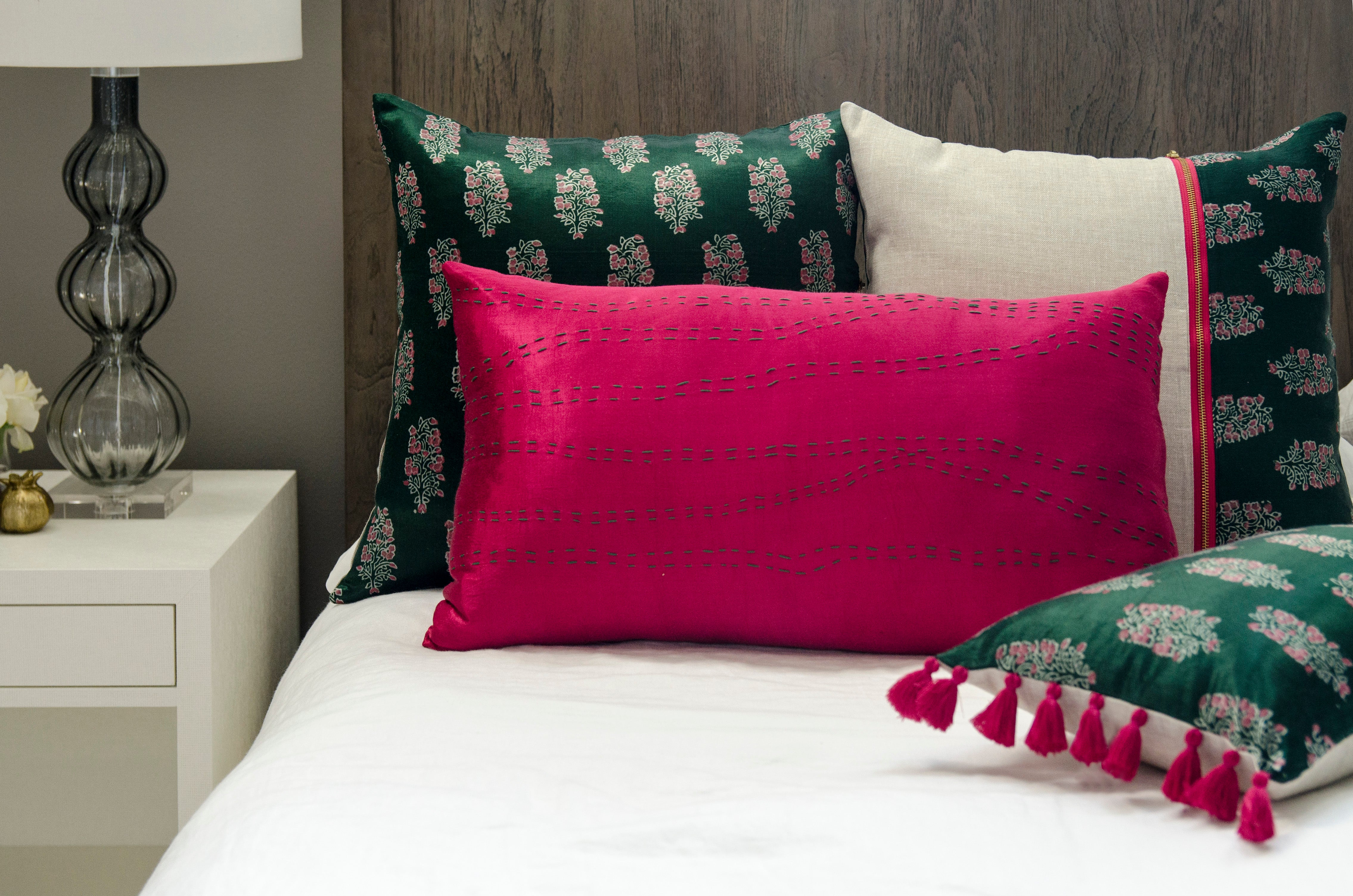 Green and pink decorative throw lumbar pillow with tassels. Handmade and block printed on a silk-cotton fabric by artisans in India. Designed for the well-travelled, modern consumer.