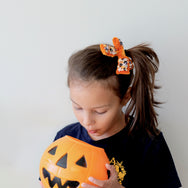 Girl with pumpkin colored velvet hair bow embellished with sequin.