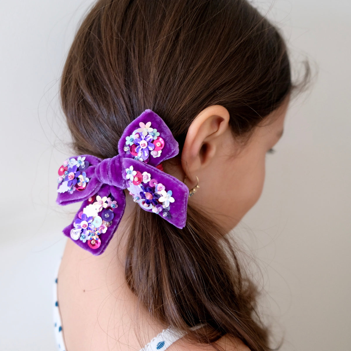 Model with velvet hair bow embellished with sequin in purple.