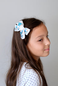 Model with velvet hair bow in white with embellished with blue sequin.
